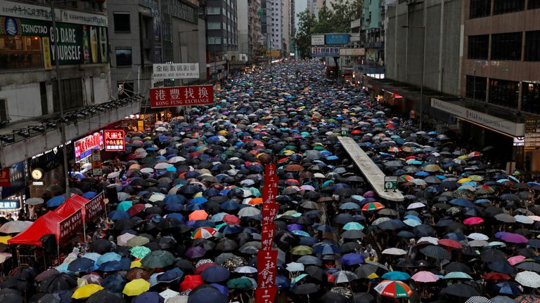 People with umbrellas up filling a street in Hong Kong