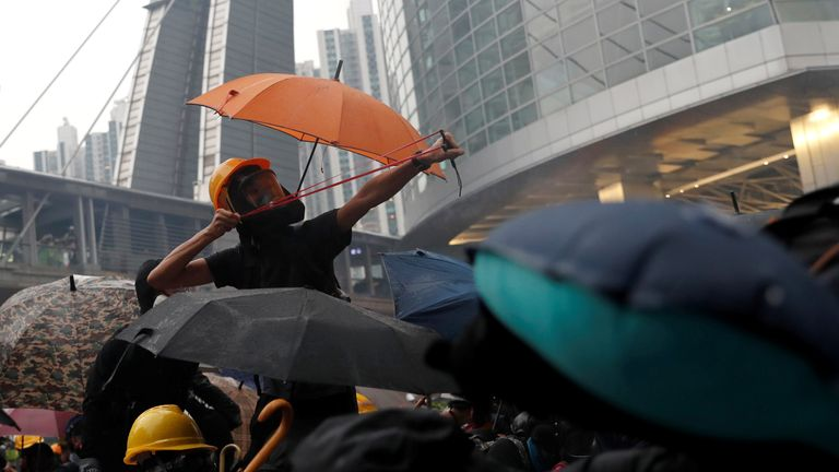 A demonstrator uses a catapult as protesters clash with riot police