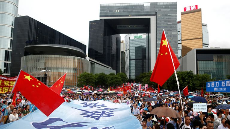 Protesters at a pro-police rally in Hong Kong raise Chinese flags