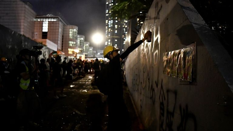 A protester sprays graffiti outside an entrance to the Tsim Sha Tsui police station