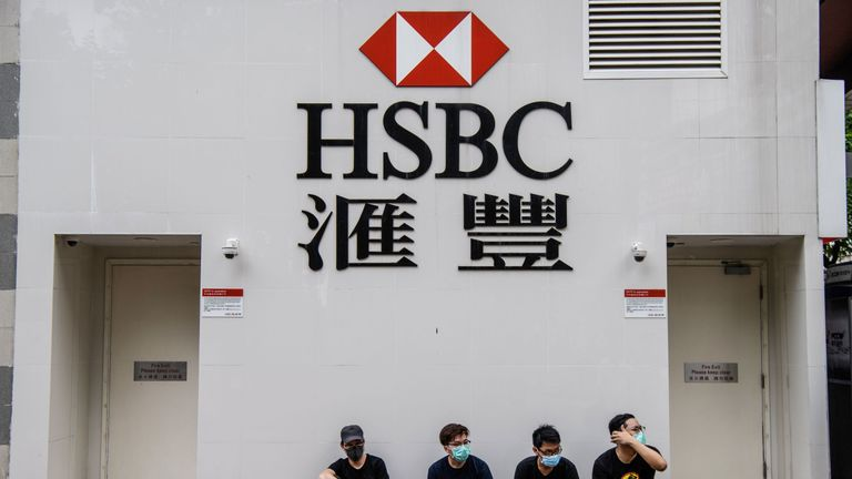 Protesters sit outside a HSBC in the Kowloon district of Hong Kong on August 11, 2019