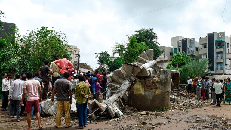 Rescue workers search for survivors after an overhead water tank collapsed due to heavy rains in Ahmedabad, kiling at least three people