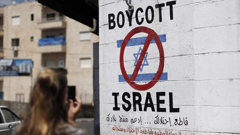 A tourist photographs a sign painted on a wall in the West Bank biblical town of Bethlehem on June 5, 2015, calling to boycott Israeli products coming from Jewish settlements. The international BDS (boycott, divestment and sanctions) campaign, that pushes for a ban on Israeli products, aims to exert political and economic pressure over Israel's occupation of the Palestinian territories in a bid to repeat the success of the campaign which ended apartheid in South Africa.