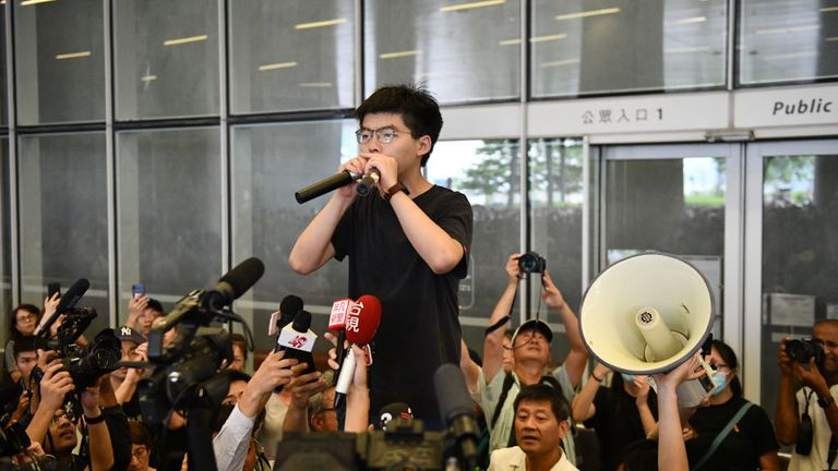 Joshua Wong speaks to a crowd outside the Legislative Council shortly after being released from prison in June