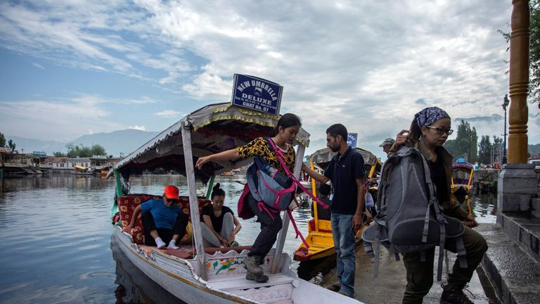 Tourists disembark from a boat on the banks of Dal Lake as they prepare to leave Srinagar