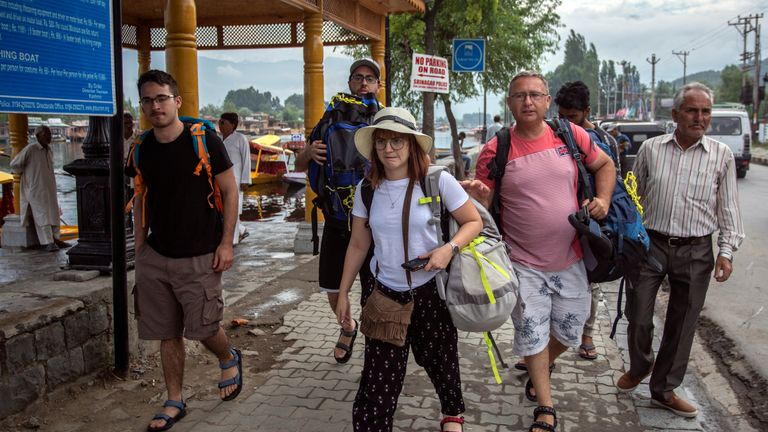 Tourists carry their luggage as they walk on the banks of Dal Lake before leaving Srinagar