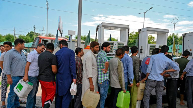 Kashmiri people stand in a queue at a petrol station in Srinagar