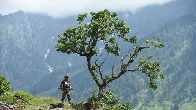 An Indian Border Security Force (BSF) soldier stands guard on top of a hill about 115 km from Srinagar in 2017