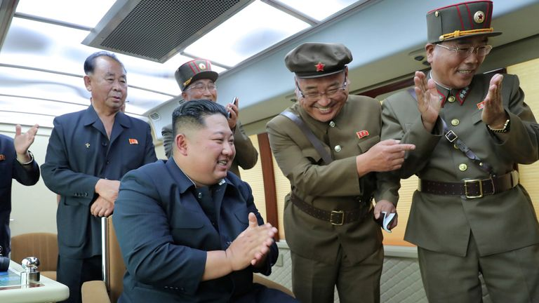 North Korean leader Kim Jong Un reacts to the test firing of a new weapon