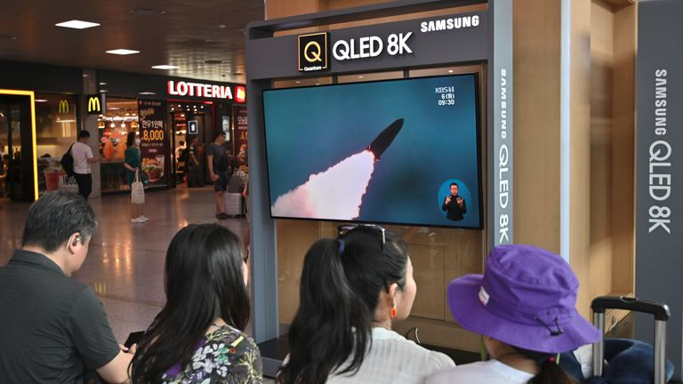 People watch a television news screen showing a file footage of North Korea's missile launch