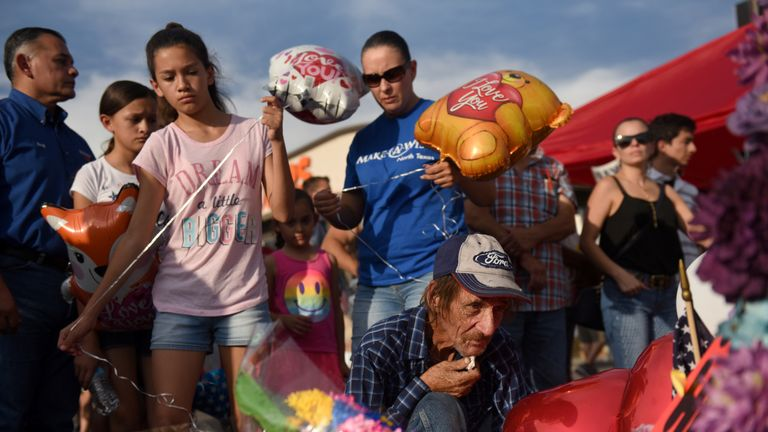 Antonio Basco has an emotional moment at the cross of his partner Margie Reckard four days after a mass shooting at a Walmart store in El Paso, Texas, U.S. August 7