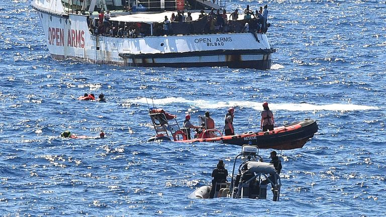 Migrants swim after jumping off the Spanish rescue ship Open Arms, close to the Italian shore in Lampedusa, Italy