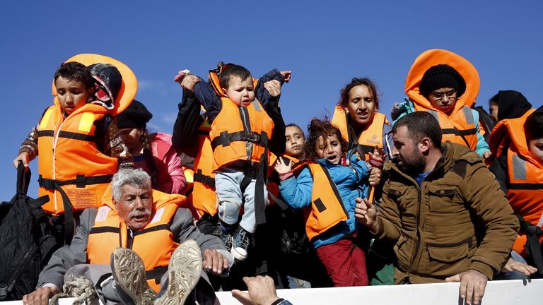 Refugees and migrants try to leave a boat as they arrive on the Greek island of Lesbos, November 26, 2015