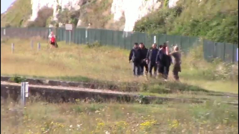 A group of suspected migrants make their way inland