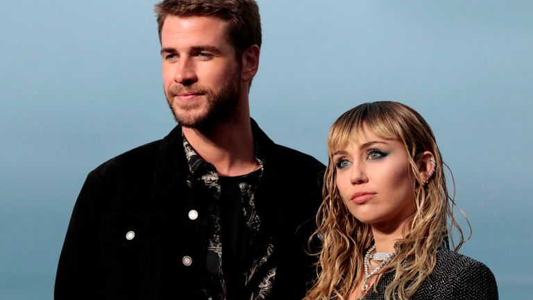 US singer Miley Cyrus and husband Australian actor Liam Hemsworth arrive for the Saint Laurent Men's Spring-Summer 2020 runway show in Malibu, California, on June 6, 2019