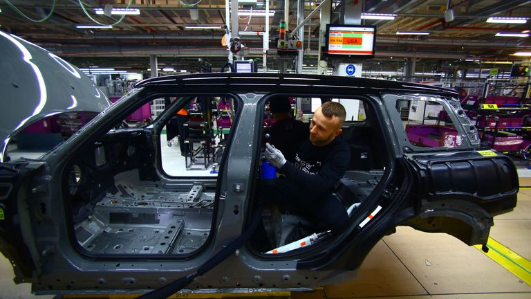 An employee fits the wiring loom to a Mini at the BMW Mini car production plant in Oxford, west of London, on January 17, 2017