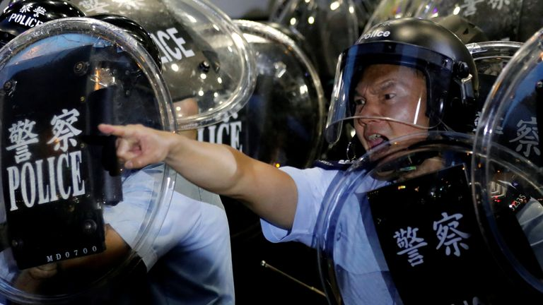 Police officers react to taunts from protesters gathered outside Mong Kok police station