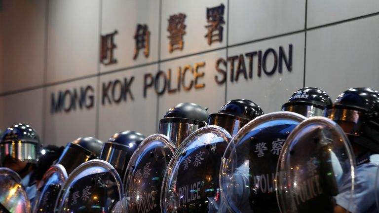 Police officers stand guard outside Mong Kok police station