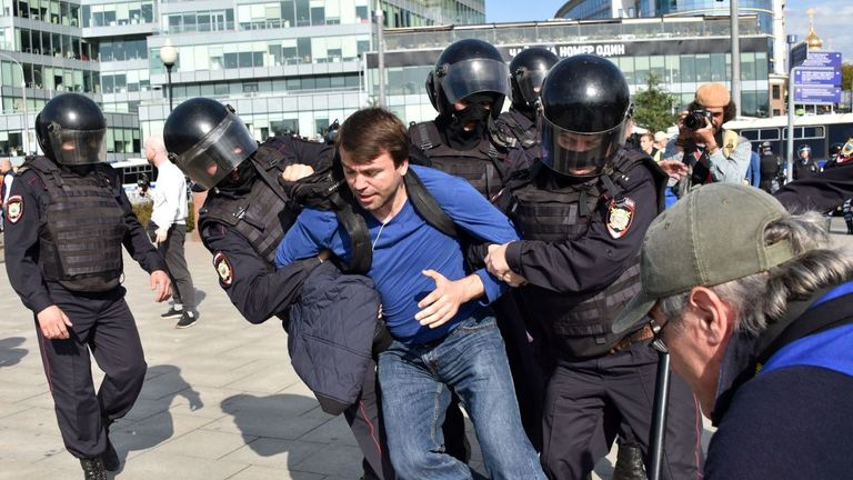 Officers detain a man during an unsanctioned rally urging fair elections
