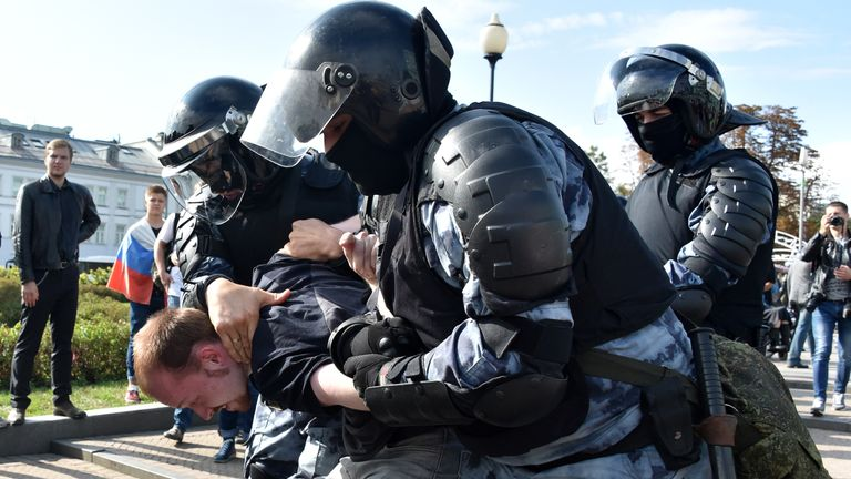 Servicemen of the Russian National Guard detain a participant of the unsanctioned rally