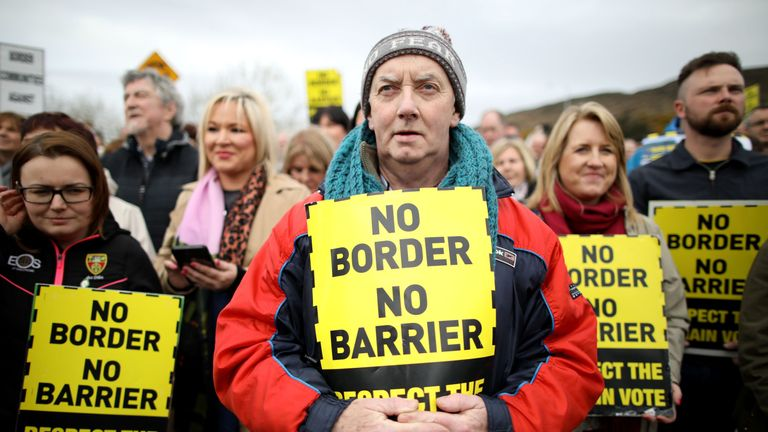 Protesters against any border between Ireland and Northern Ireland because of Brexit hold placards at the Carrickcarnan border between Newry in Norther Ireland and Dundalk in the Irish Republic on March 30, 2019. - British Prime Minister Theresa May on Saturday mulled a possible fourth attempt to get her Brexit agreement through parliament, faced with the growing risk of a chaotic no-deal exit in less than two weeks' time.