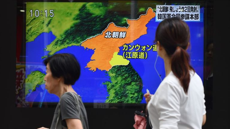 Pedestrians in Japan walk past a roadside television screen reporting on North Korea's projectile launch