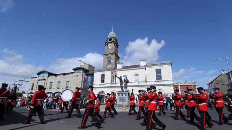 A band march past the Ulster Defence Force memorial in Lisburn city centre