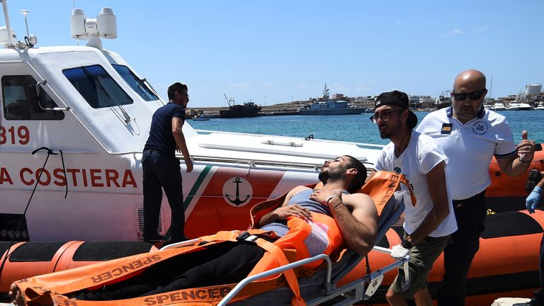A migrant who jumped off of Open Arms is carried on stretcher in Lampedusa