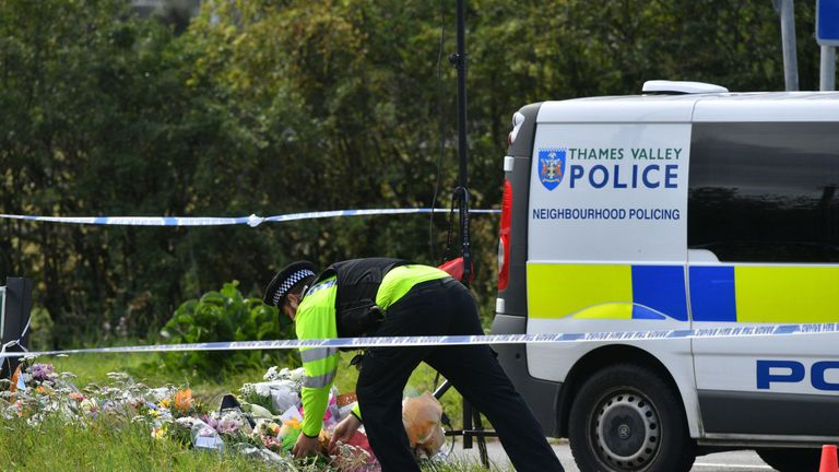 A police officer laying flowers at the scene of PC Harper's death