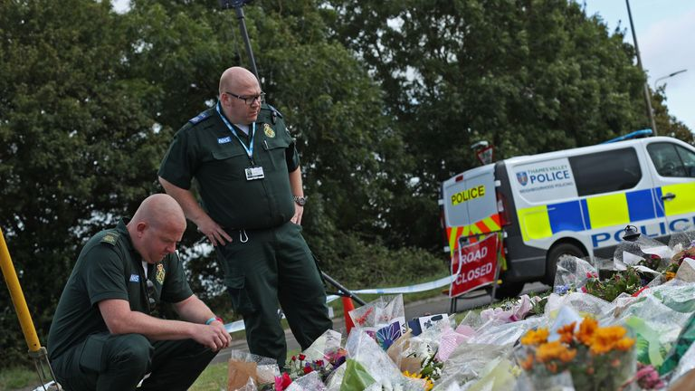 Ambulance paramedics pay their respects in front of tributes left at the scene near Ufton Lane, Sulhamstead, Berkshire