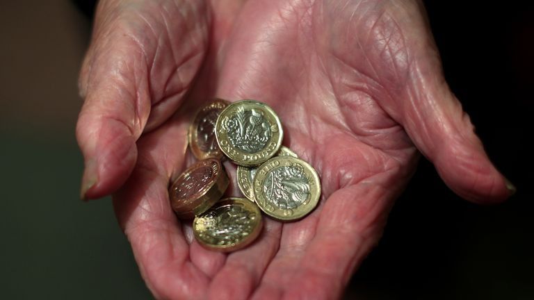 An elderly woman holding pound coins in her hands in Poole, Dorset.