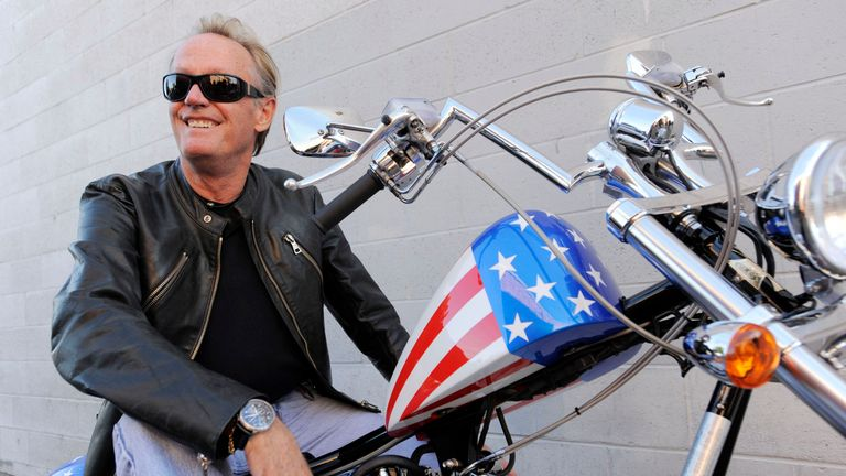 Peter Fonda, poses atop a Harley-Davidson motorcycle in Glendale