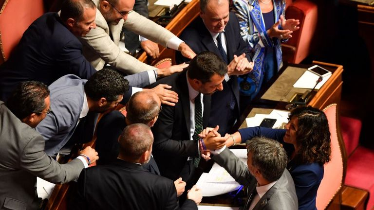 Members of the far-right League party congratulates Deputy Prime Minister and Interior Minister Matteo Salvini (C) following his speech at the Italian Senate, in Rome, on August 20, 2019