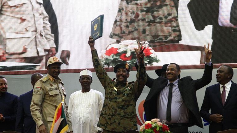 Sudan's protest leader Ahmad Rabie (2nd-R), flashes the victory gesture alongside General Abdel Fattah al-Burhan (C), the chief of Sudan's ruling Transitional Military Council