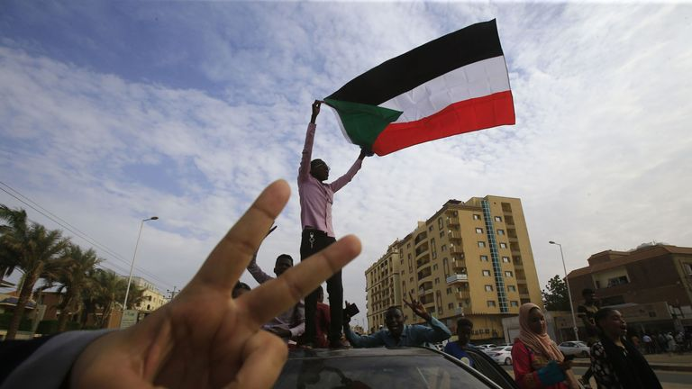 A Sudanese protester waves a national flag as another flashes the V for victory gesture as they take part in a demonstration called for by the Sudanese Professionals Association (SPA) to denounce the July 29 Al-Obeid killings, in the capital Khartoum on August 1, 2019