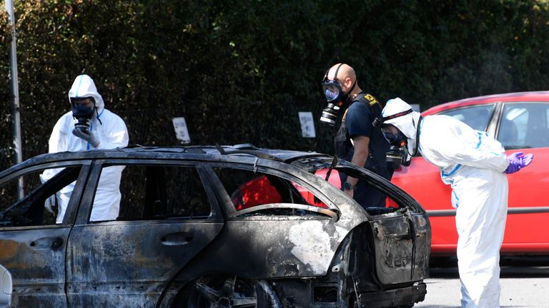 Forensic officers inspected a burned out car nearby after the woman was killed