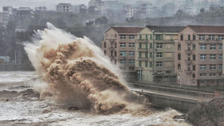 Waves hit a sea wall in front of buildings in Taizhou, China's eastern Zhejiang province