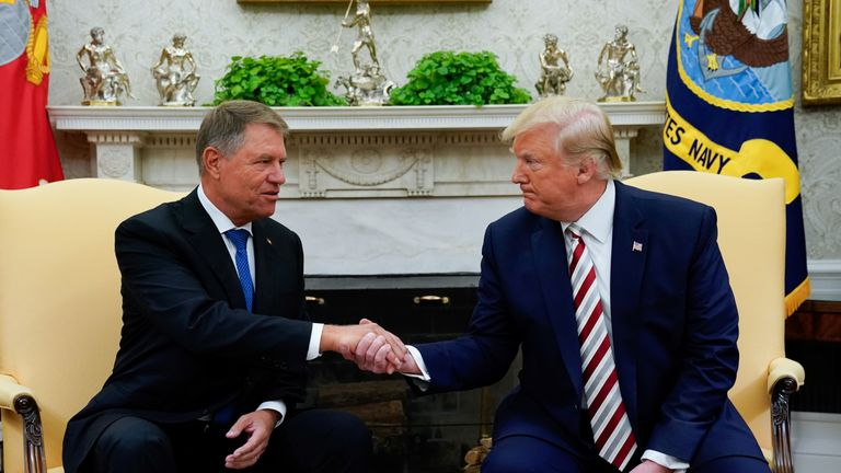 Donald Trump shakes hands with Romania's President Klaus Iohannis during a meeting in the Oval Office