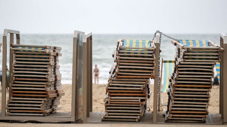 Deckchairs are stacked up on the sea front on Bournemouth beach in Dorset