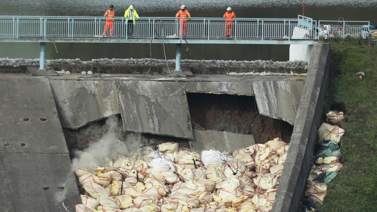 A bag of concrete is thrown onto the damaged Toddbrook Reservoir near the village of Whaley Bridge, Derbyshire, after heavy rainfall. PRESS ASSOCIATION Photo. Picture date: Saturday August 3, 2019. Photo credit should read: Yui Mok/PA Wire