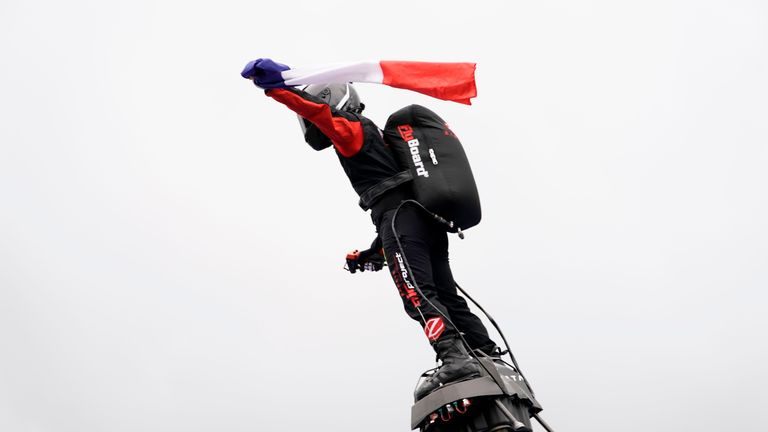 Franky Zapata on his jet-powered hoverboard or 'Flyboard' flies with the French national flag during a performance in tribute to late BWT Arden's French driver Anthoine Hubert, who died in an accident during a Formula 2 race on August 31, at the Spa-Francorchamps circuit in Spa on September 1, 2019, before the start of the Belgian Formula One Grand Prix. (Photo by Kenzo TRIBOUILLARD / AFP)        (Photo credit should read KENZO TRIBOUILLARD/AFP/Getty Images)