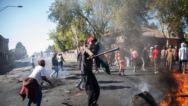 A man screams holding a stick in front a burning piece of furnitureduring a riot in the Johannesburg suburb of Turffontein on September 2, 2019 as angry protesters loot alleged foreign-owned shops today in a new wave of violence targeting foreign nationals. (Photo by Michele Spatari / AFP)        (Photo credit should read MICHELE SPATARI/AFP/Getty Images)