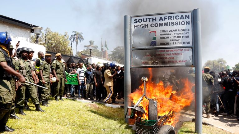 Zambia's unniversity students burn the sign outside the South African Embassy in Lusaka on September 4, 2019 during a demonstration to protest against xenophobic attacks on foreign nationals in the Rainbow Nation. (Photo by SALIM DAWOOD / AFP)        (Photo credit should read SALIM DAWOOD/AFP/Getty Images)