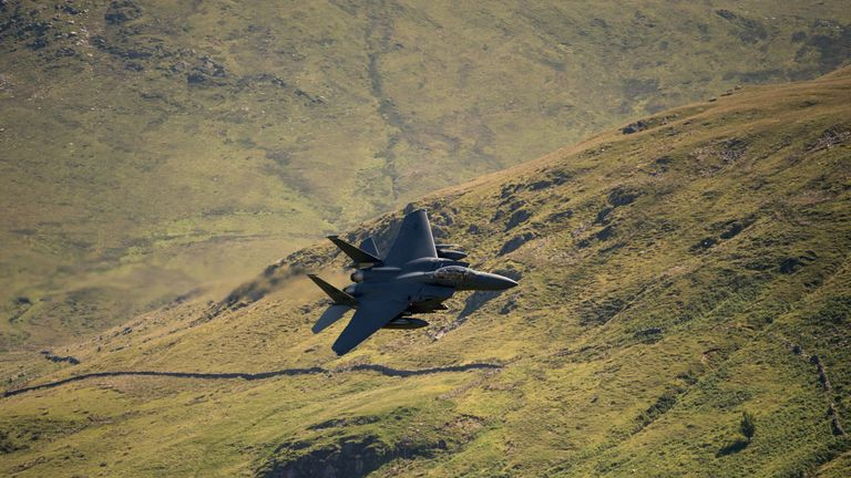 A United States Air Force (USAF) F-15 fighter jet travels at low altitude through the 'Mach Loop' series of valleys near Dolgellau, north Wales on June 26, 2018. - The Mach Loop valleys, situated between Dolgellau and Machynlleth, are regularly used by the military for operational low flying training which can take place as low as 76 metres from the nearest terrain. (Photo by OLI SCARFF / AFP)        (Photo credit should read OLI SCARFF/AFP/Getty Images)