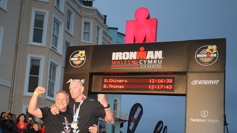 TENBY, WALES - SEPTEMBER 15:  Former Welsh rugby International captain Gareth Thomas (R) reacts after finishing Ironman Wales on September 15, 2019 in Tenby, Wales. (Photo by Nigel Roddis/Getty Images for IRONMAN)