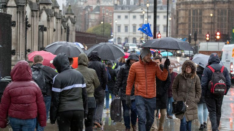 Pedestrians use umbrellas to shield from the rain Westminster, London as Storm Gareth sweeps across the country.
