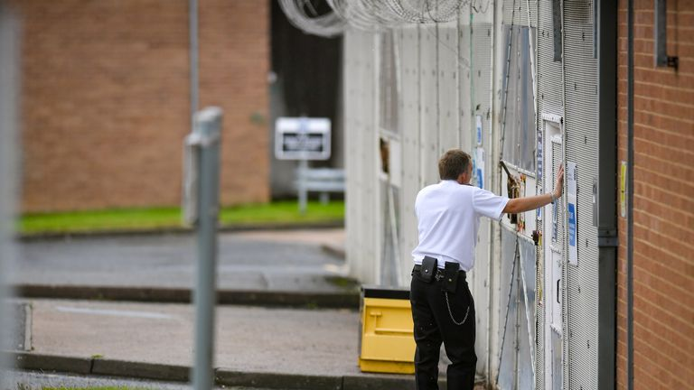 A general view of an officer next to a gate at HMP Long Lartin, near Worcester, where order has been restored after a siege at the prison last night, when a group of inmates took over part of a building, the Ministry of Justice said.
