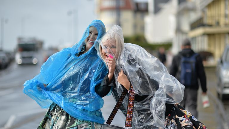 Two women wear plastic ponchos to keep dry in the wind and rain during the Porthcawl Elvis Festival in south Wales.