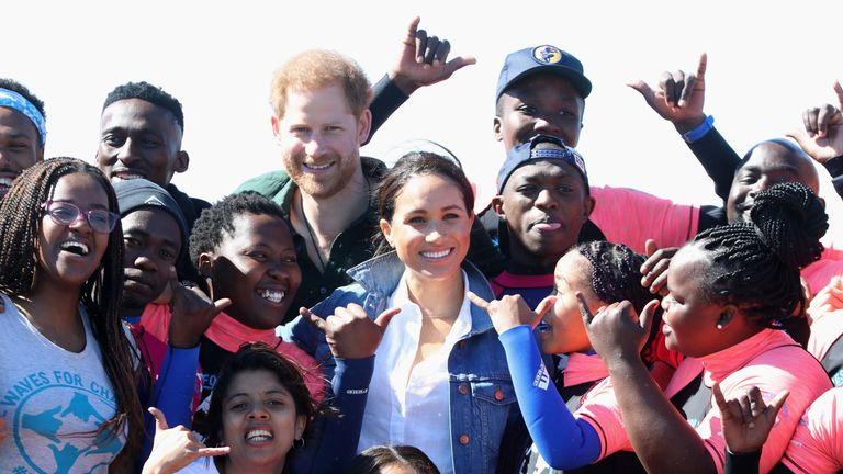 The Duke and Duchess of Sussex pose for a photograph with surf mentors during a visit to Waves for Change at Monwabisi Beach in Cape Town, on day two of their tour of Africa.