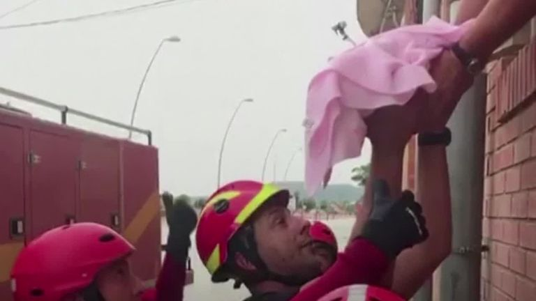 A baby is rescued from floods in Spain